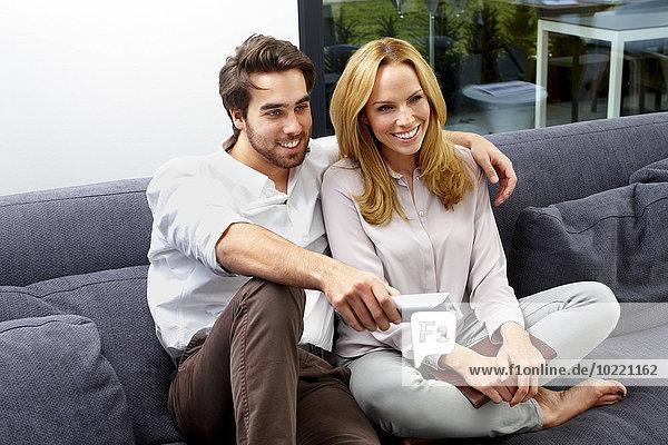 Glückliches Paar sitzt zusammen auf der Couch und schaut TV-Show