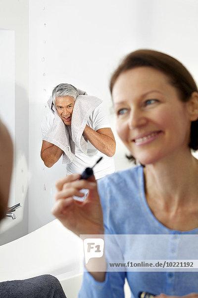 Ein reifer Mann wischt sich das Gesicht mit einem Handtuch ab und eine Frau schminkt sich davor.