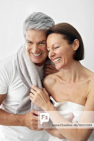 Glückliches Paar mit Handtüchern Kopf an Kopf vor weißem Hintergrund
