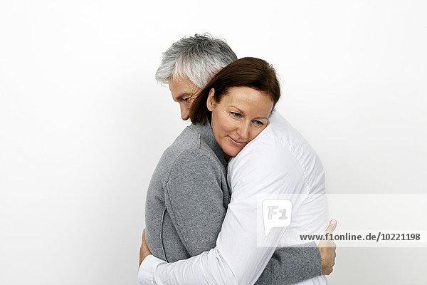 Paar umarmt sich vor weißem Hintergrund