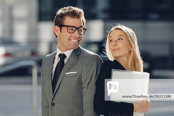 Lächelnder Geschäftsmann und Geschäftsfrau im Freien Rücken an Rücken