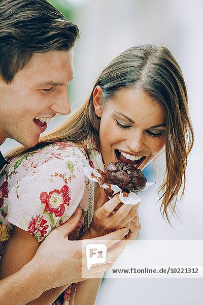 Glückliches junges Paar beim Essen von Schokoladenmuffin