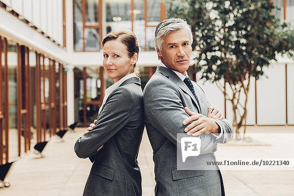Reife Geschäftsmänner und -frauen stehen Rücken an Rücken mit Blick auf die Kamera.