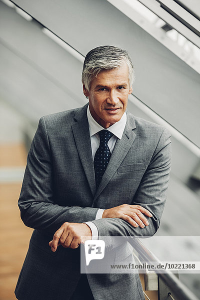 Der reife Geschäftsmann am Geländer
