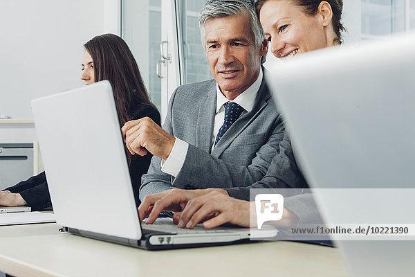 Geschäftsleute im Büro arbeiten am Laptop