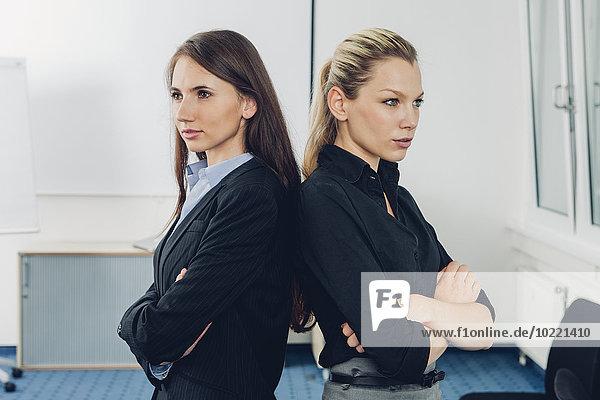 Zwei junge Geschäftsfrauen  die Rücken an Rücken stehen.