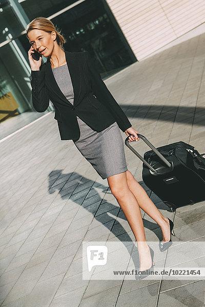 Geschäftsfrau am Handy unterwegs mit Koffer