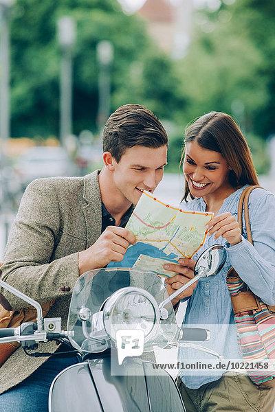 Junges Paar auf dem Motorroller auf der Karte
