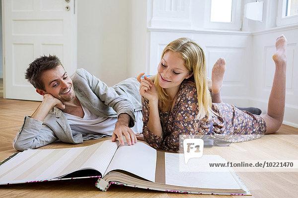 Junges Paar liegt auf dem Boden und wählt Tapete aus einem Katalog aus.