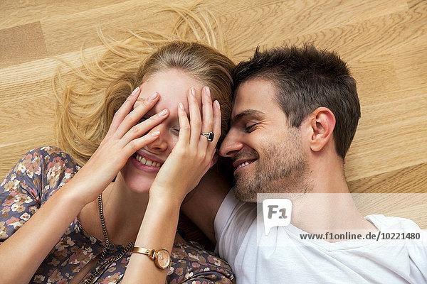 Draufsicht eines glücklichen jungen Paares auf dem Boden liegend