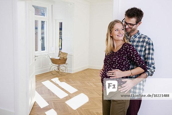Junger Mann umarmt schwangere Frau im neuen Zuhause mit Kinderwagen im Hintergrund Junger Mann umarmt schwangere Frau im neuen Zuhause mit Kinderwagen im Hintergrund