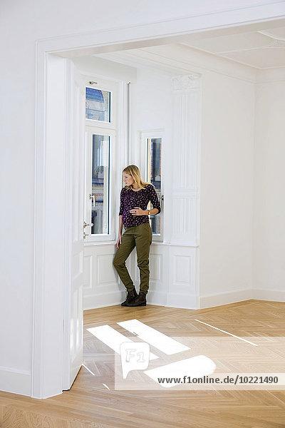 Junge schwangere Frau in einem leeren Raum mit Blick aus dem Fenster Junge schwangere Frau in einem leeren Raum mit Blick aus dem Fenster