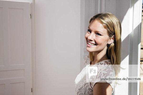 Lächelnde blonde junge Frau schaut weg