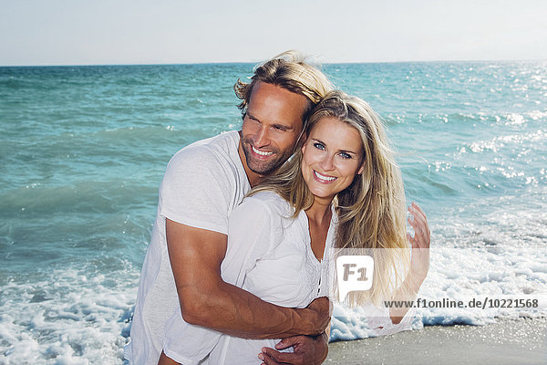 Spanien  Mallorca  glückliches Paar  das sich am Meer umarmt