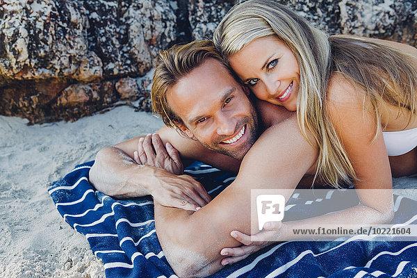 Lächelndes Paar am Strand liegend