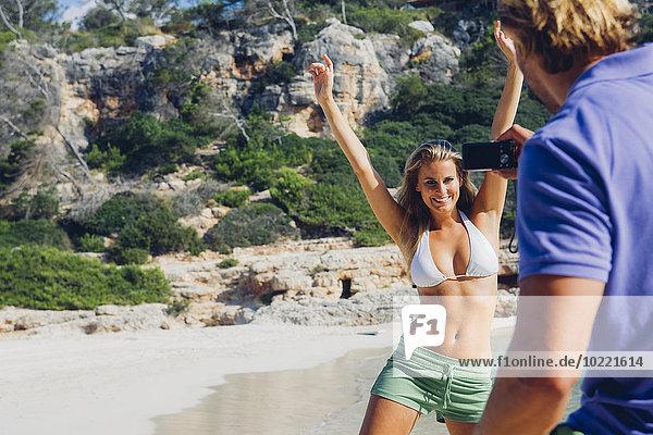 Spanien  Mallorca  Frau am Strand posiert für Mann mit Kamera