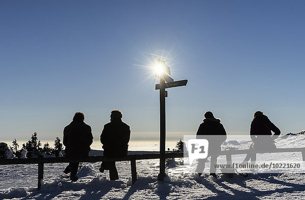 Germany  Saxony-Anhalt  four hikers sitting side by side enjoying view from Brocken