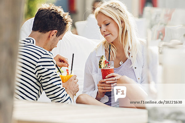 Young couple sitting in an outdoor cafe with glasses of fresh juice