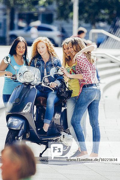 Vier Freundinnen mit Motorroller