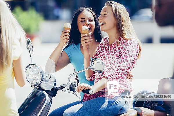 Two teenage girls with motor scooter and ice cream cones