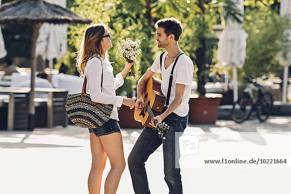 Loving young couple with guitar and bunch of flowers on the street