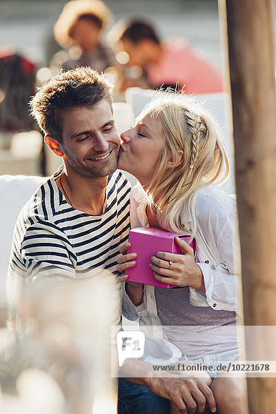 Young woman holding a gift kissing her boyfriend at outdoor cafe
