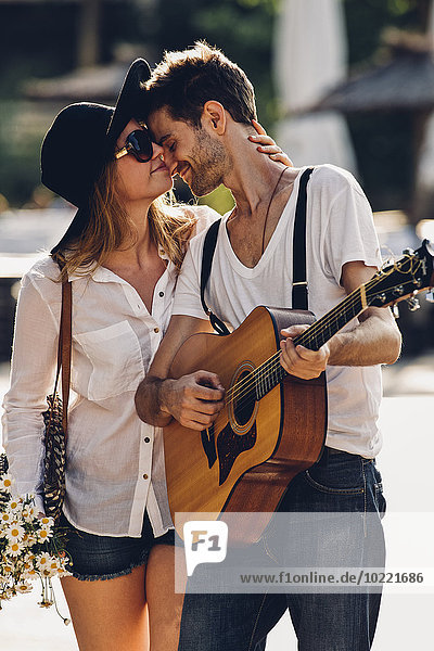 Loving young couple with guitar and bunch of flowers