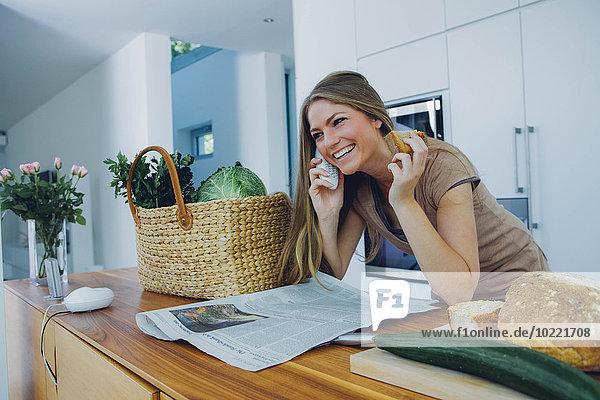 Glückliche Frau am Telefon in der Küche nimmt Lebensmittel aus der Tasche