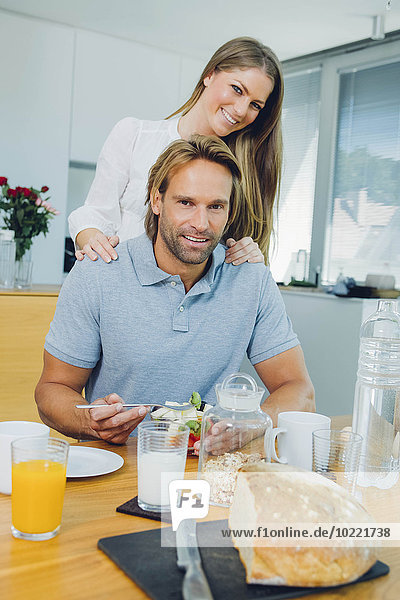 Porträt eines Paares beim Essen am Küchentisch