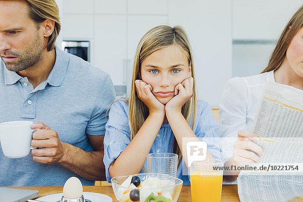 Frustriertes Mädchen mit abgelenkten Eltern am Frühstückstisch