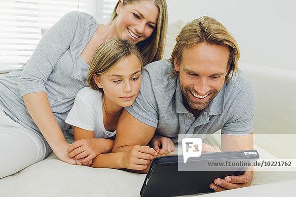 Glücklicher Vater  Mutter und Tochter liegen auf der Couch und teilen sich ein digitales Tablett.