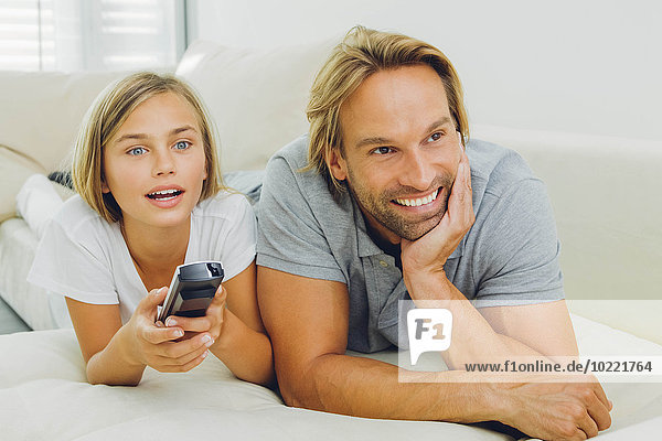Father and daughter lying on couch watching TV