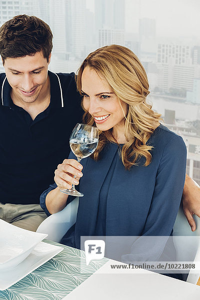 Lächelndes Paar am Esstisch mit Frau beim Weißweintrinken