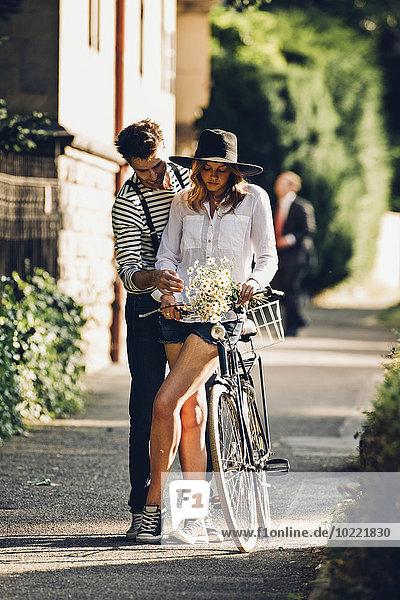 Junges Paar mit Fahrrad und Blumenstrauß auf dem Bürgersteig stehend