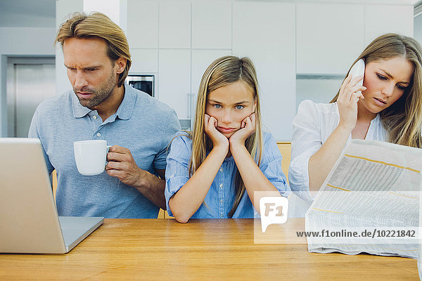 Frustriertes Mädchen mit abgelenkten Eltern bei Tisch