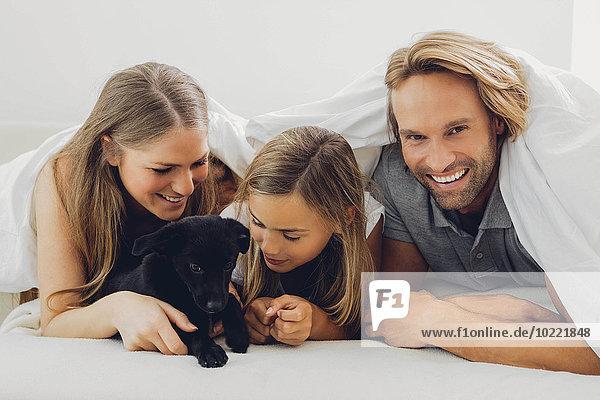 Glücklicher Vater  Mutter und Tochter mit Welpe im Bett