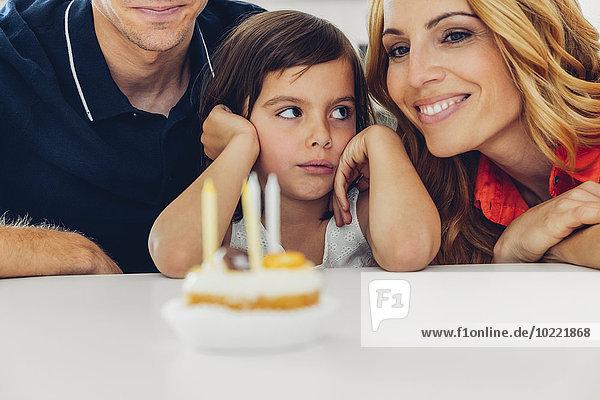 Familie mit Tochter feiert Geburtstag mit Kerzen auf Kuchen