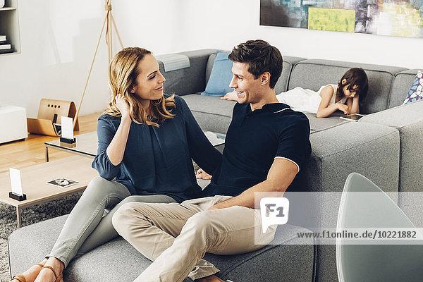 Lächelndes Pärchen im Wohnzimmer mit Tochter mit digitalem Tablett im Hintergrund