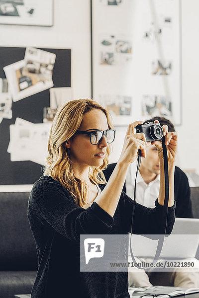 Frau im Wohnzimmer mit Kamera und Mann im Hintergrund