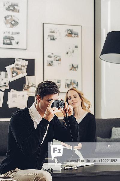 Mann im Wohnzimmer fotografiert mit Frau im Hintergrund