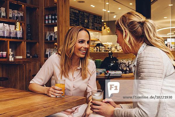 Zwei Freundinnen mit Getränken  die in einem Coffee-Shop kommunizieren.