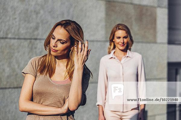 Seriöse blonde Frau im Freien mit Frau im Hintergrund