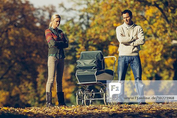 Reserviertes Paar steht mit gekreuzten Armen und schaut auf den Kinderwagen im Herbstpark.
