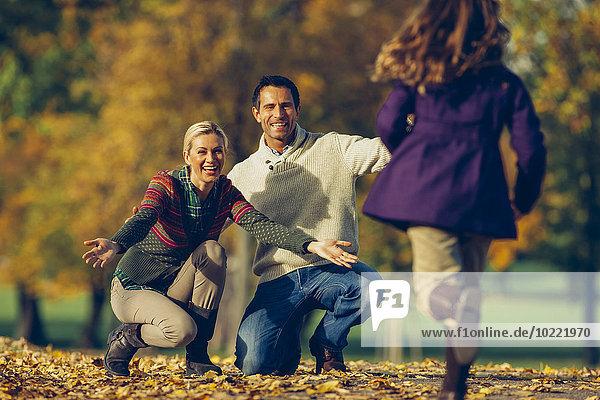 Tochter  die an einem sonnigen Herbsttag zu ihren Eltern im Park rennt.