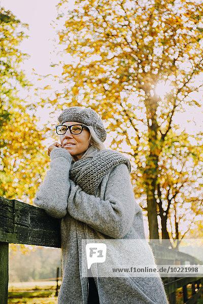 Portrait of woman wearing grey knitwear in an autumnal park