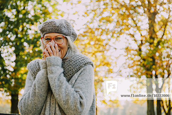 Portrait of laughing woman in an autumnal park