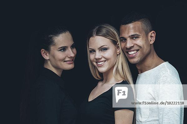 Gruppenbild von zwei jungen Frauen und jungen Männern vor schwarzem Hintergrund