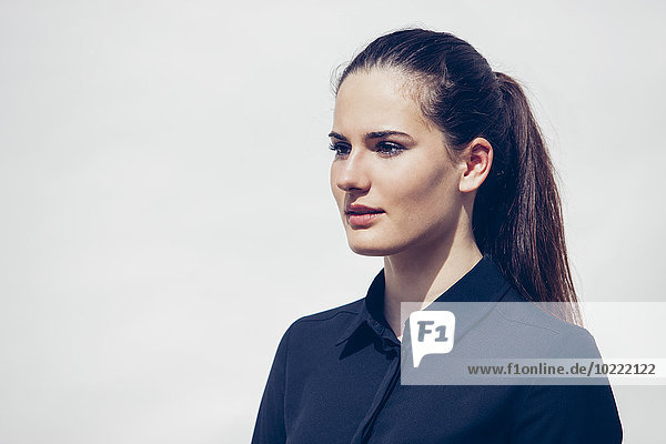 Portrait of young woman with ponytail in front of white background