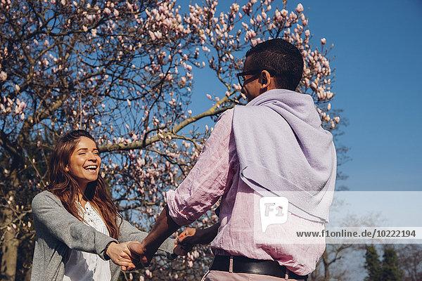 Glückliches junges Paar hält sich im Park an den Händen.