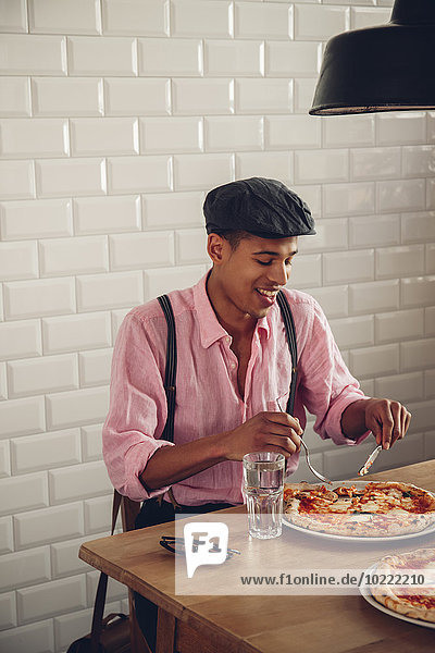 Young man eating pizza in restaurant